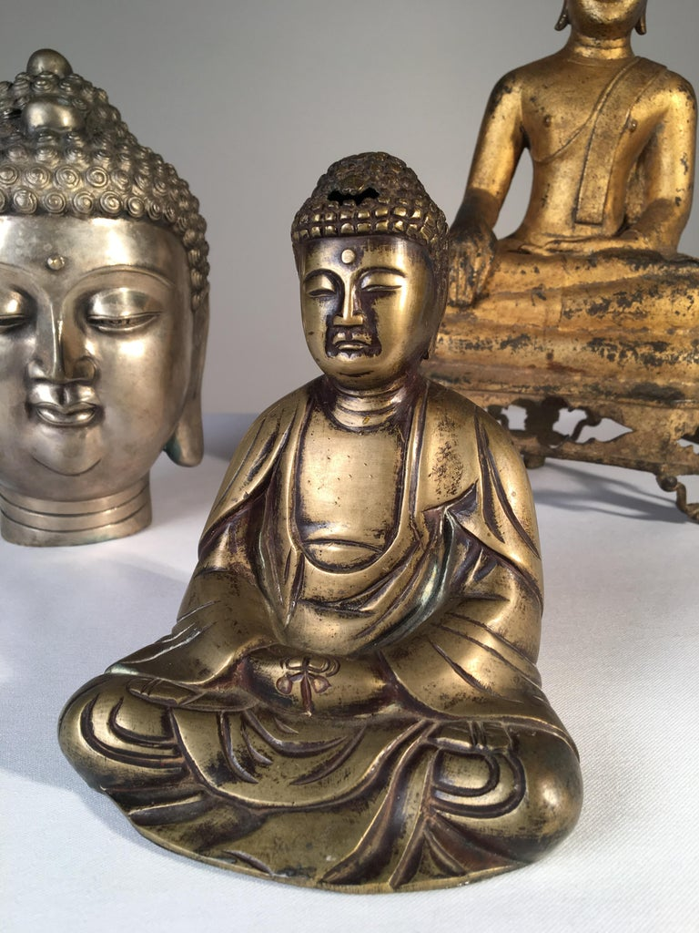 A collection of 3 Buddhas in various metals, including an antique seated gilt bronze Thai Buddha.