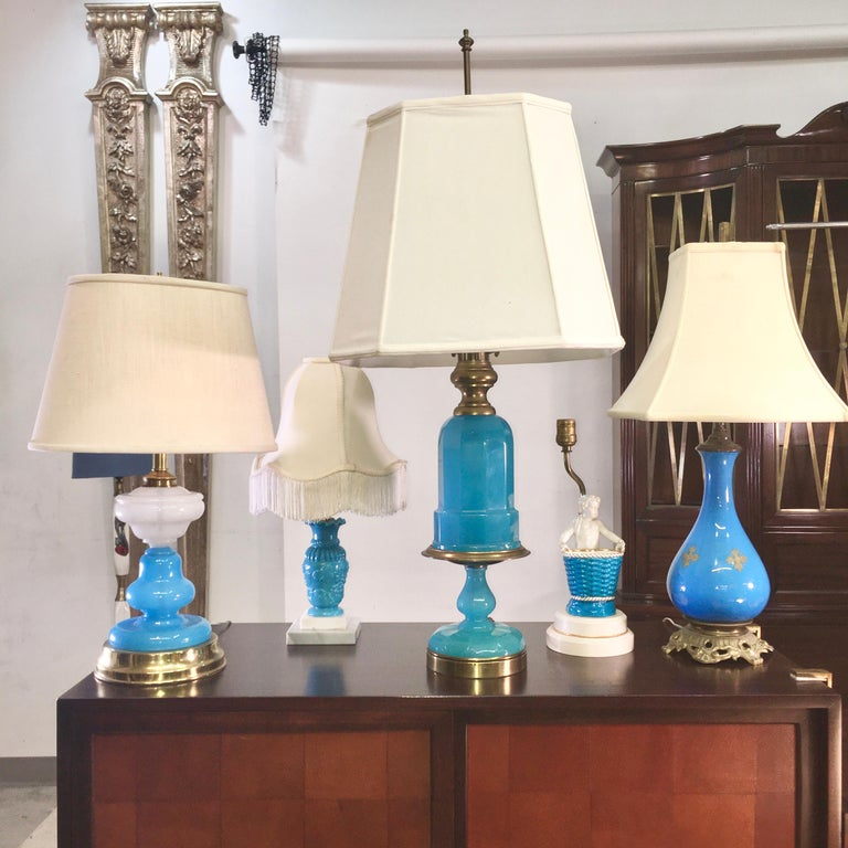 Unique grouping of five lamps from the mid-20th century in complementary shades of blue, the largest of which is a turquoise blue opaline Cenedese glass lamp mounted on gilt brass. All of these are from the estate of Sarasota artist Miriam Shorr.
