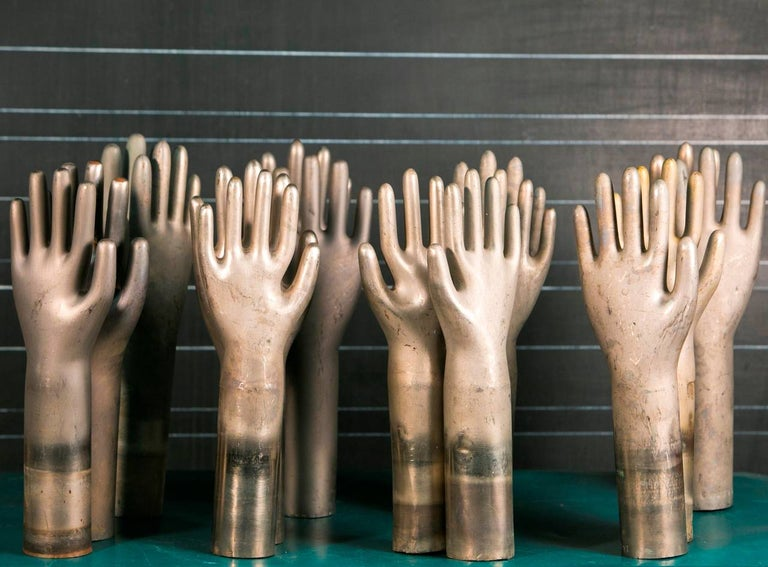 Heavy cast aluminum glove molds from France, circa 1940s. Price is for the remaining set of five. We can provide pictures of the specific remaining five upon request.