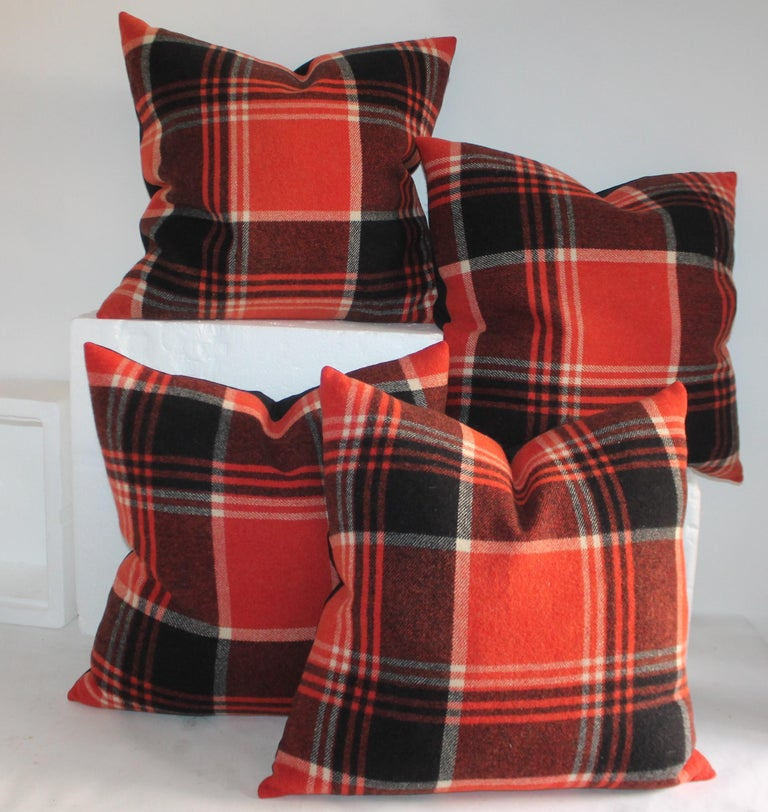 Collection of four black and red plaid pillows in great condition. The textiles were pulled from a vintage camp blanket made from wool. Beautiful pattern to the pillow with a vintage linen backing.