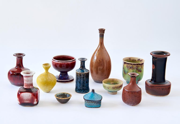 Each vessel in this collection of twelve miniatures is a unique, signed studio piece in stoneware by the great Swedish ceramist, Stig Lindberg. They have a variety of forms, and a diverse palette of glaze colors, and are collectively quite