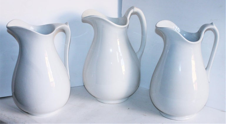 These three white 19th century ironstone water pitchers are great to use for vases of flowers or just display with your ironstone collection. All in mint condition.