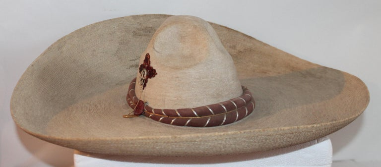 Collection of three handmade Mexican sombreros. In pristine condition with original label. Leather straps make the bans around the crown of two of the sombreros and the other has a beautiful handmade geometric pattern around the brim and the crown.