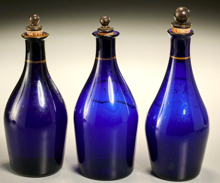 Rare George III cobalt blue bottles, circa 1820. Three total, Rum, Rum, and Brandy. In great condition for their age, each with a silver and cork stopper and gilt lettering and decoration. Each measures approximately 9
