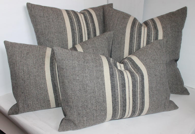 Collection of two different size pillows in grey flannel wool woven fabric. The backings are in grey cotton linen.