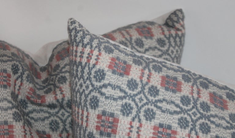 These fine hand woven coverlet pillows in blue grey with salmon trim. The backings are in homespun cotton linen. Sold as a group of four.