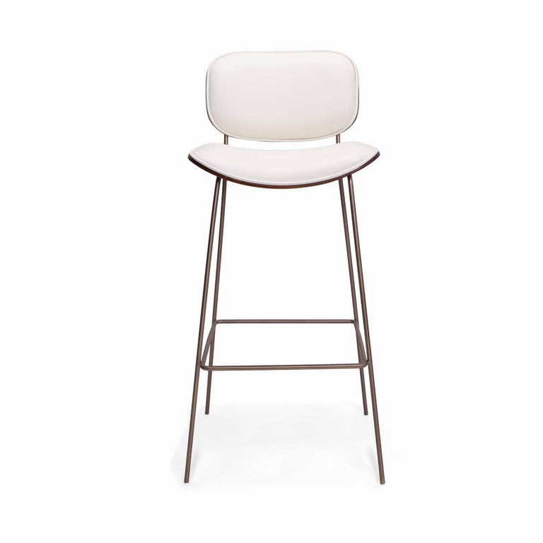 Bar stool with an elegant metal structure. Seat and back finished in beautiful polished ebony or oak and upholstered in leather. Available in bar and counter height. Customizable to your specifications.