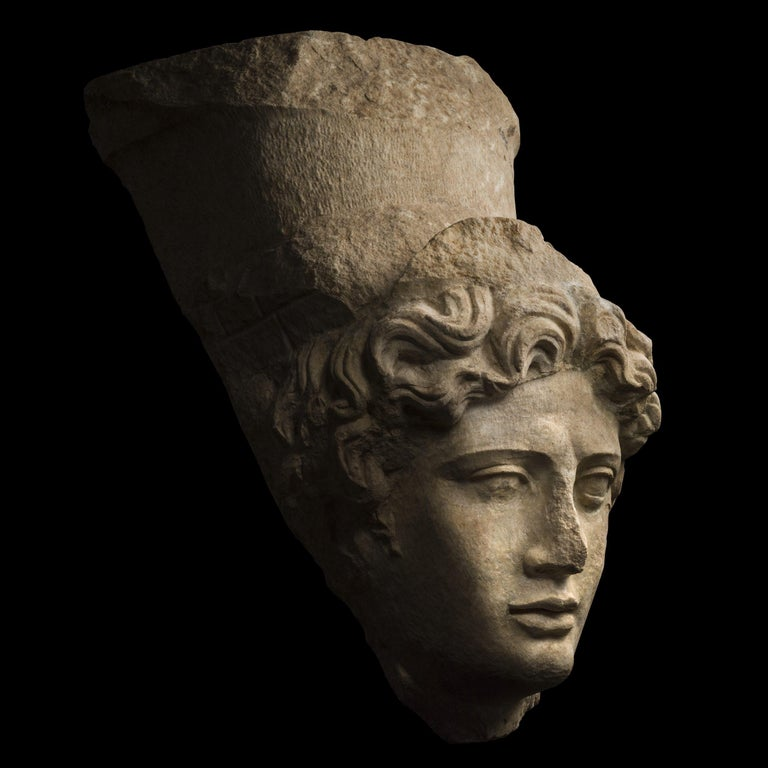 This impressive, larger than life size female head with a crown represents the goddess Tyche, or Fortuna, the Graeco-Roman personification of luck and chance. Her regular and well-delineated features, noble proportions, and a perfect oval of the