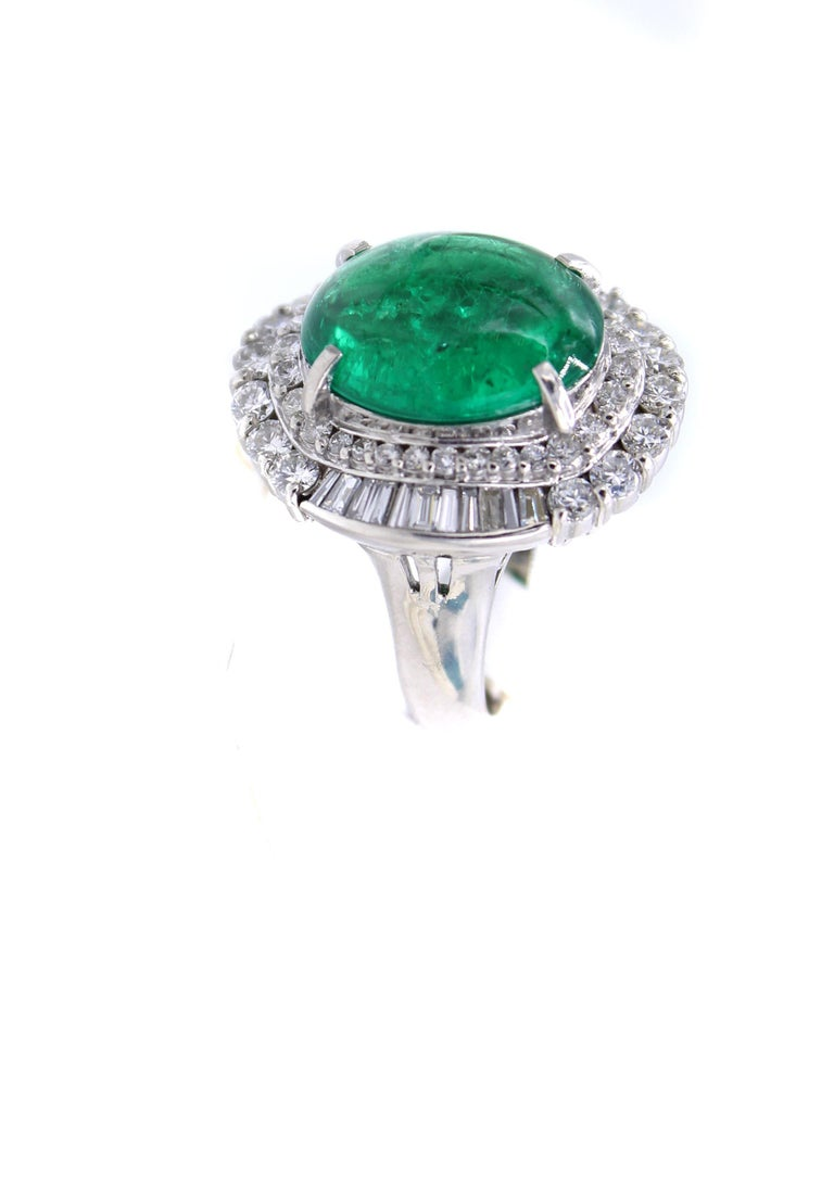 A luscious forest green cabochon emerald weighing 5.01 carats is the centerpiece of this bold platinum 1970s ring. The emerald comes with a report from the AGL. Embellishing the center gem are beautifully matched bright white round brilliant cut and
