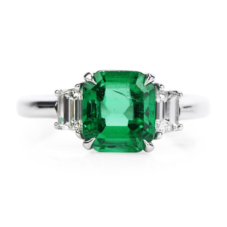 Deep green minor enhanced AGL Certified Colombian Emerald & Diamond engagement ring.  Crafted in solid platinum, the center is adorned by an Incredible AGL-certified Colombian Emerald with minor coating treatment, emerald cut, prong set, weighing