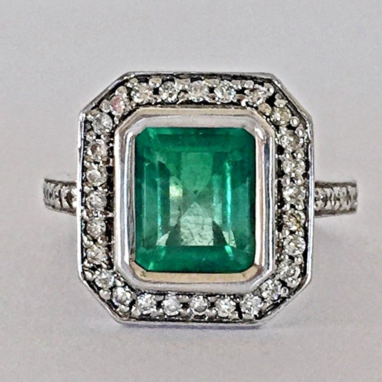 This elegant Art Deco engagement style ring features a 3.50-carat Colombian emerald emerald cut displaying a vibrant green color. It is accented by a shimmering halo of white round brilliant cut diamonds as well as half way sparkling diamonds on