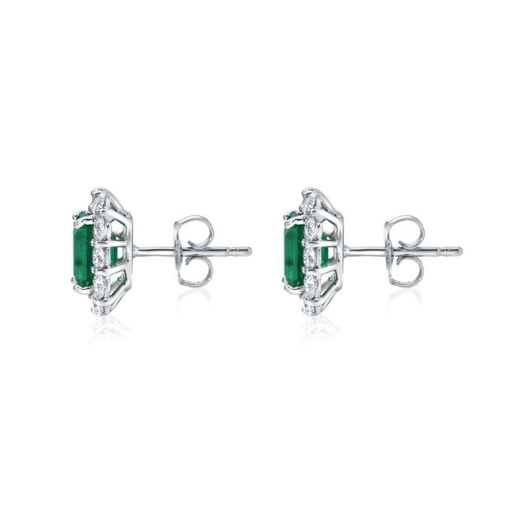 Colombian Emerald stud earrings, featuring a pair of emerald cuts weighing a total of 2.27 carats, surrounded by a total of 1.32 carats of round brilliant diamonds, in 18K white gold. Returns are accepted and paid by us within 7 days of