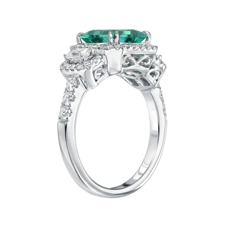 Very lively medium green 1.75 carat Colombia Emerald ring in 18K white gold, flanked by a pair of emerald cut diamonds and surrounded by round brilliant diamonds weighing a total of 0.83 carats. Size 6.5. Re-sizing is complimentary upon