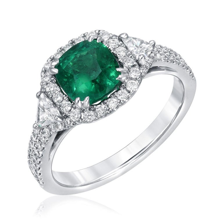 Cushion cut Colombian Emerald ring set with a 1.39 carat Emerald and a total of 0.63 carats of trillion and round brilliant diamonds. This Emerald engagement ring or cocktail ring is crafted in 18K white gold. Emerald ring size 6.5. Resizing is
