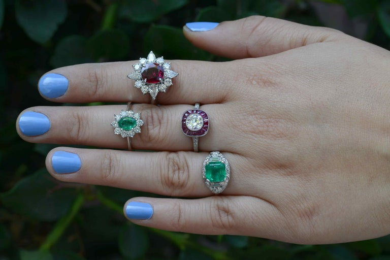The Newport Engagement Ring. A stunning and rare 1920's Art Deco masterpiece centered by a stunning emerald of nearly 2 1/2 cts, likely Colombian, from Muzo. Graced with a most vivid and intense grass-green color, she seems to glow with an inner