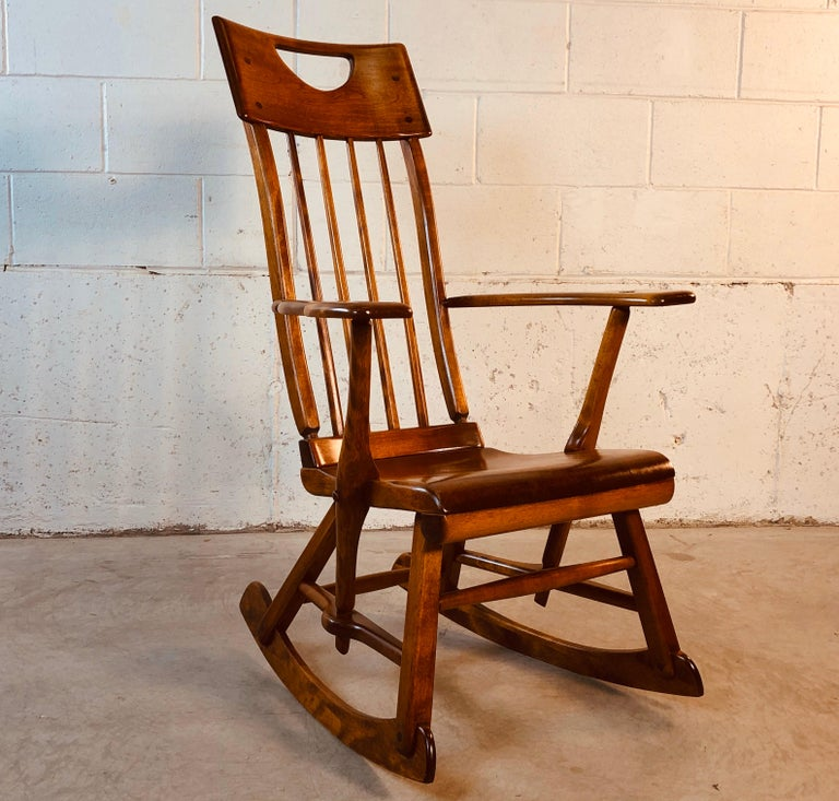 Colonial American style solid maple wood high-back rocking chair designed by Herman de Vries for Sikes Furniture Co. This rocking chair is from the 1930s and is all handmade. The chair has been restored and refinished and is in excellent condition.