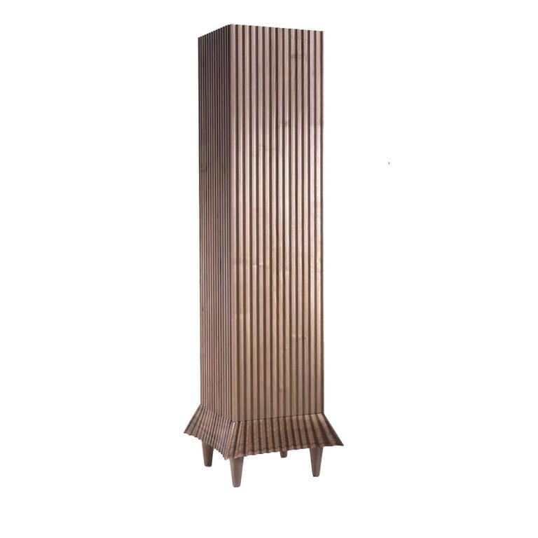This stunning tall cabinet is part of a limited edition of 10 pieces designed by Ugo La Pietra. The narrow silhouette of this container, crafted of wood with a natural walnut honey finish is highlighted by the stunning texture of its outer frame,