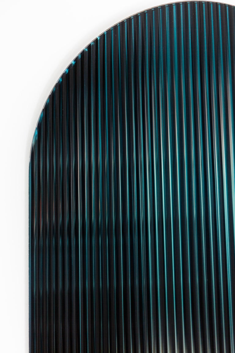 A reflective, colored patterned glass panel designed to add a palette of color to spaces. The piece disperses light through it's rippled reflective surface creating a blended dimensional palette of color. The piece visually shifts creating different