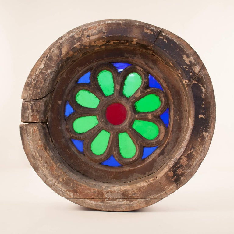 A rare and beautiful piece of colonial history, this circular window is fabricated from vibrant blue, green and red translucent glass set in a thick, three-piece teak wood frame. Likely salvaged from a Goa heritage home, this circa 1900 window is in
