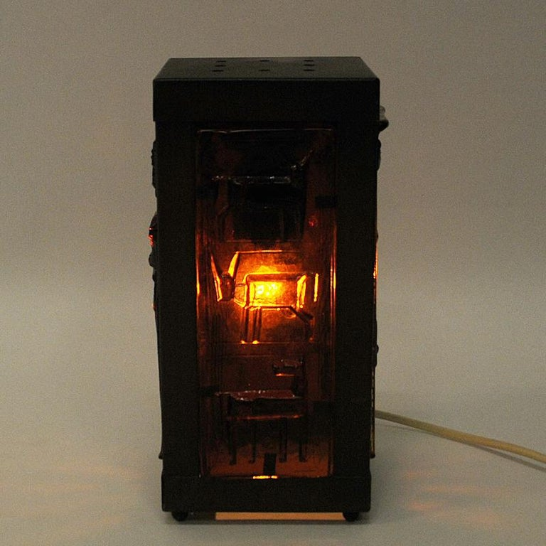 Lovely rectangular table lamp of glass and copper by Erik Höglund, Sweden, 1960s. A glass table lamp with four decorated amber brown glass panels (Kosta Boda) of people and animals in which gives a beautiful red light when lit. Brown copper frames