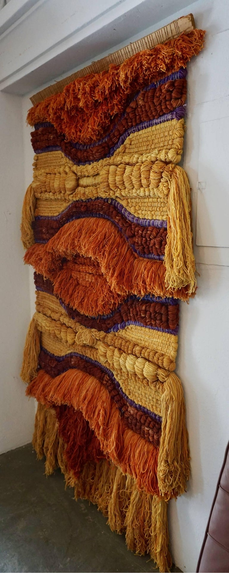 Woven, dyed and tufted yarns in bold colors of orange, burnt sienna and purple violet. Excellent example of 1960s fiber art.
