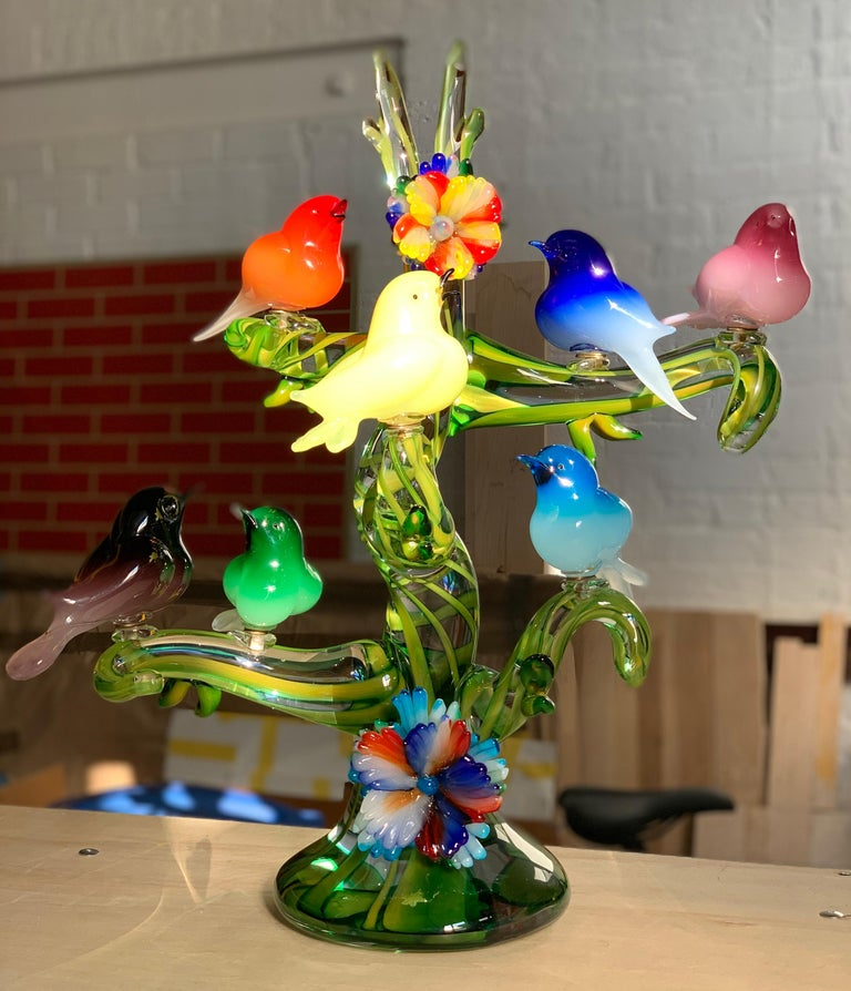 Colorful murano glass birds in a tree sculpture, Enrico Cammozzo, Italy, 1970s. Gorgeous monumental piece. Murano Italian art glass bird sculpture. Enrico Cammozzo (Italian, born 1965). Seven birds perched on a tree bearing two large glass flowers.