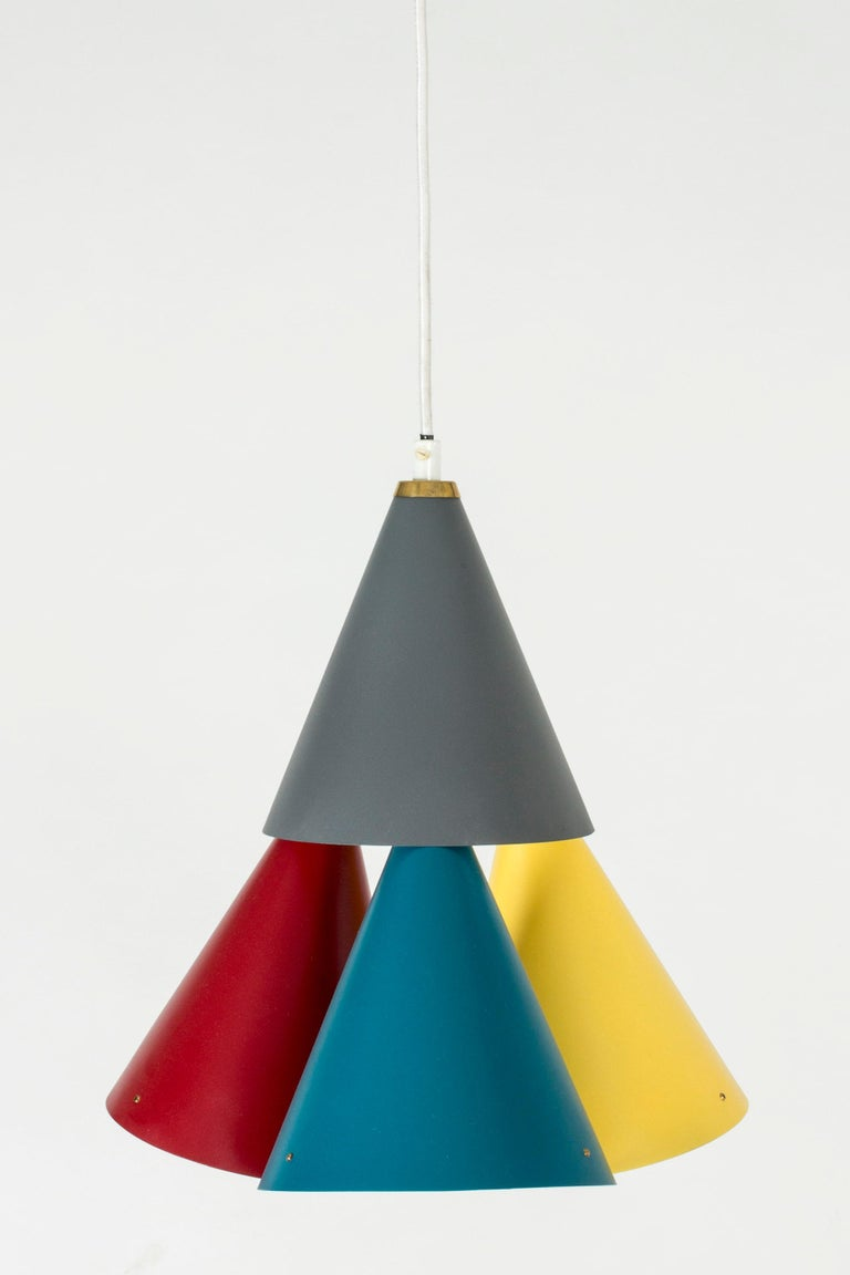 Colorful metal pendant lamp by Svend Aage Holm-Sørensen, with four lampshades in a conical formation. Grey, dark red, yellow and petrol blue give a lively expression to the clean design. Brass details where the shades are joined. Textile cord.