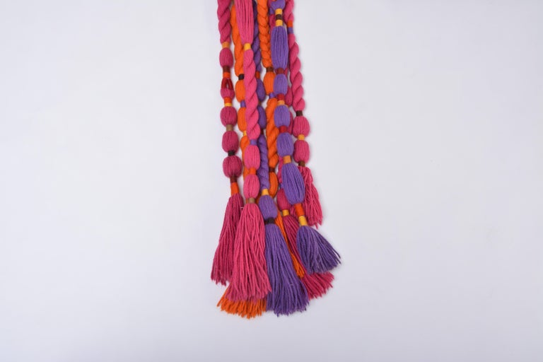 This gorgeous wall rug was designed in the 1970s by artist Ewald Kröner and manufactured by his own Label Schloss Hackhausen in Germany. Rectangular wall rug with eight long tassels made of wool in purple, pink and orange. A great example of a 1970s