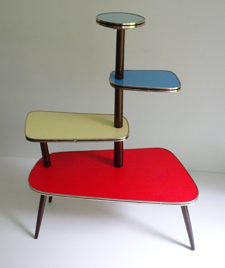 Colourful large Mid-Century Modern tripod kidney 1950s-1960s flower / plant stand A multilevel colored flower table/plant stand, it has 1 great plate and 3 smaller plates, made out of wood with a bright colored laminate and brass / black banding.