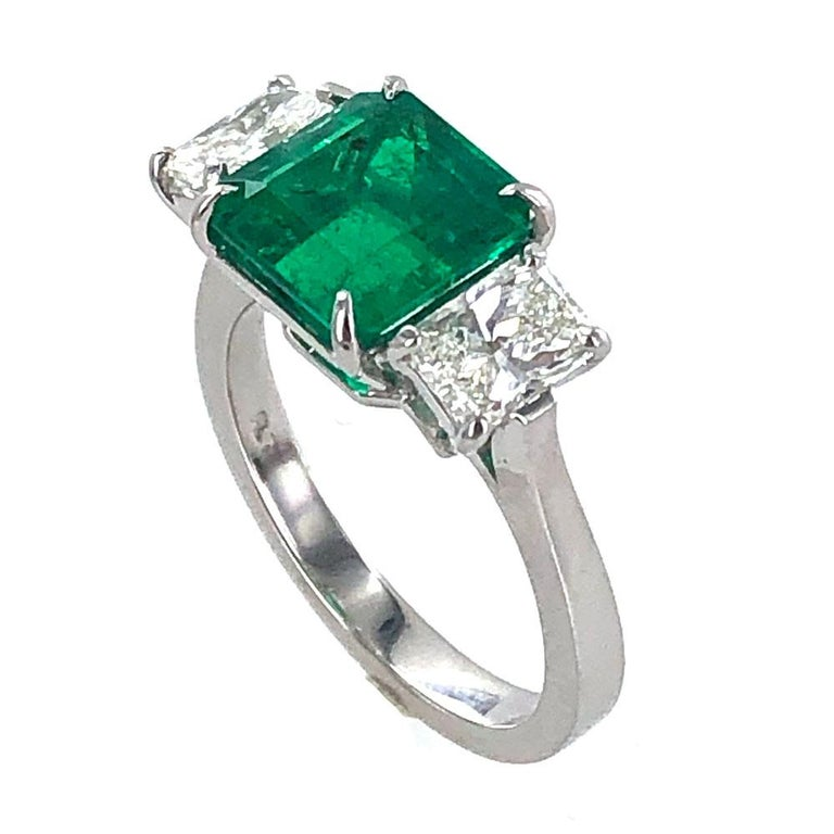 Magnificent deep green emerald and diamond ring crafted in platinum. The 3.11 carat step cutColombian emerald has been certified by the GIA F1 minor. The emerald is flanked by two radiant cut diamonds weighing approximately 1.10 carat total weight.