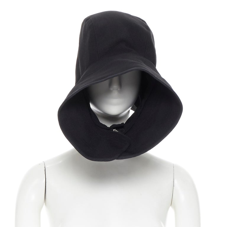 COMME DES GARCONS black zip toggle button upside down brim snood hat Brand: Comme Des Garcons Designer: Rei Kawakubo Model Name / Style: Snood hood Material: Polyester Color: Black Pattern: Solid Closure: Zip Extra Detail: Designed to look like a