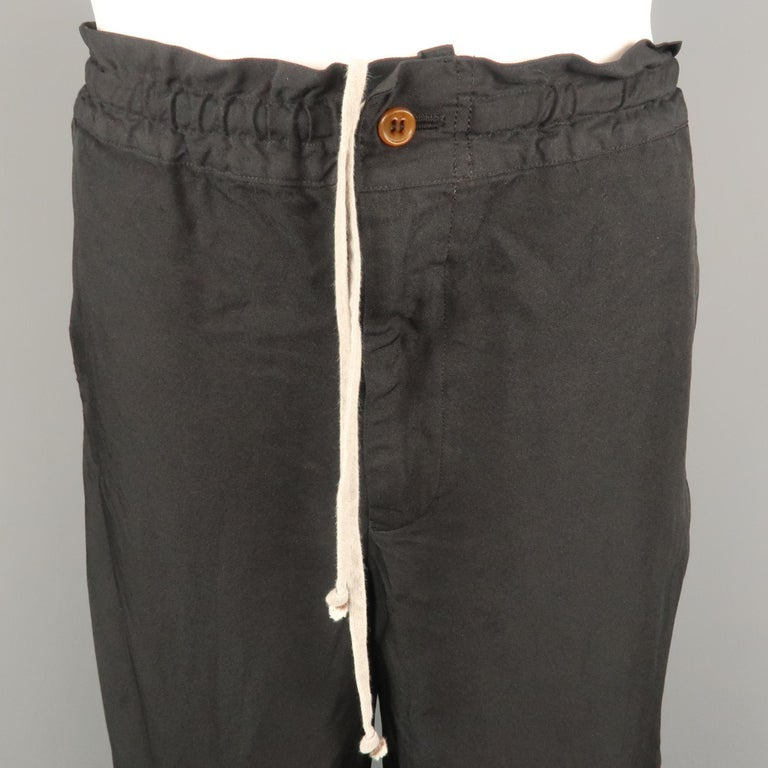 COMME des GARCONS HOMME PLUS casual pant comes in a black polyester featuring a regular fit and drawstring style. Made in Japan.   Very Good Pre-Owned Condition. Marked: L   Measurements:   Waist: 34 in. Rise: 10 in. Inseam: 29 in.