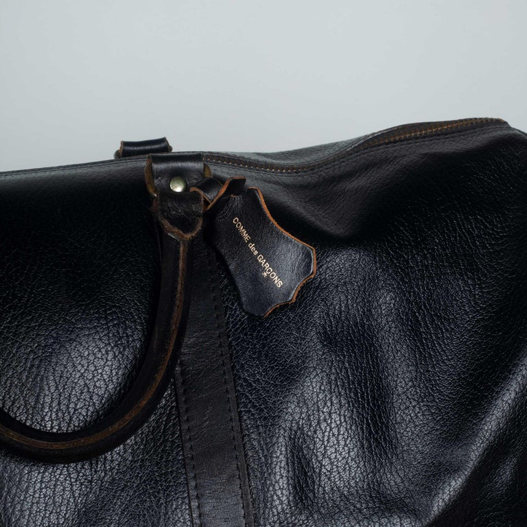 Comme des Garçons large, black leather Boston bag from Japan with zip closure, natural cowhide interior and leather tag with logo. This stylish vintage travel bag can be used as a carry-on for short trips or long. It is large enough to hold garments