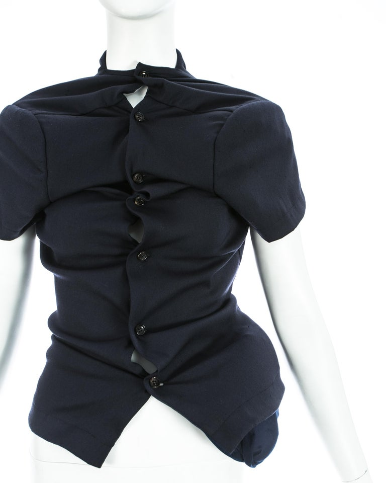 Comme des Garcons; Navy blue stretch wool jacket with net lining and integral pillows positioned on the hip. Button closures throughout and exaggerated shoulder pads.   'Body Meets Dress' / 'Lumps and Bumps' Spring-Summer 1997