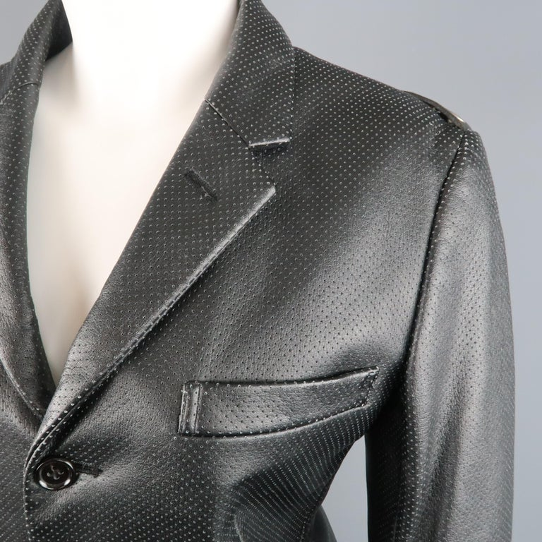 COMME des GARCONS blazer comes in perforated vegan faux leather with a notch lapel, three button, single breasted front, flap pockets, and grommet belt back detail along the shoulders. Made in Japan.   Excellent Pre-Owned Condition. Marked: S