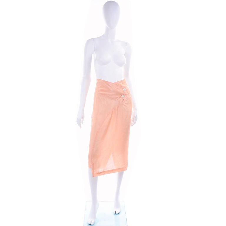 This is a great vintage 1990's Comme Des Garçons peach rayon skirt. The skirt has a double button closure ib the wide waistband. We love the way the waist dips to a slight V.  There is a back slit and asymmetrical hemline. This is such an easy to