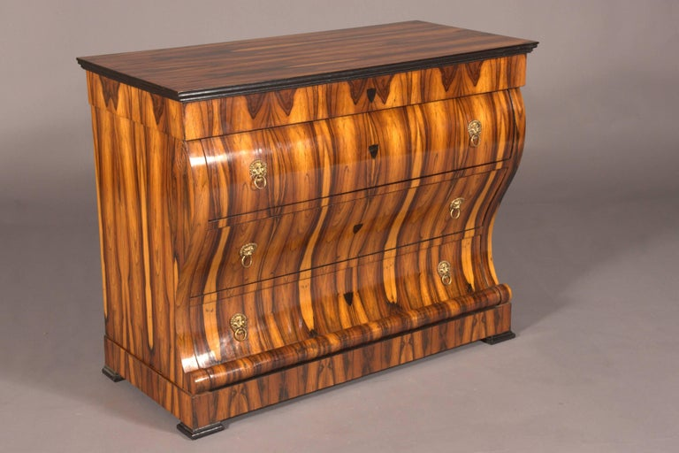 Exotic Indian veneer on massive fir wood. Strong curly form, high rectangular, exceptionally strongly curved, vierschübiger body on plinth feet. Slightly protruding, profiled cover plate. This form is known in numerous literatures, including G.