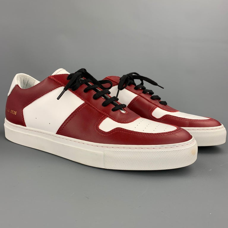 COMMON PROJECTS shoes comes in a white & burgundy leather featuring a rubber sole and a lace up closure. Made in Italy.   Very Good Pre-Owned Condition. Marked: EU 44  Outsole:  12 in. x 4 in.