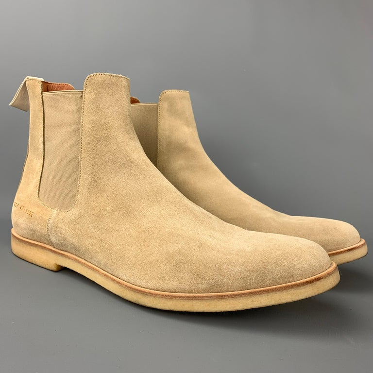 COMMON PROJECTS boots comes in a beige suede featuring a chelsea style, slip on, and a creep sole. Made in Italy.  Very Good Pre-Owned Condition. Marked: 1897 47 1302 Original Retail Price: $530.00  Measurements:  Length: 13 in. Width: 4.5