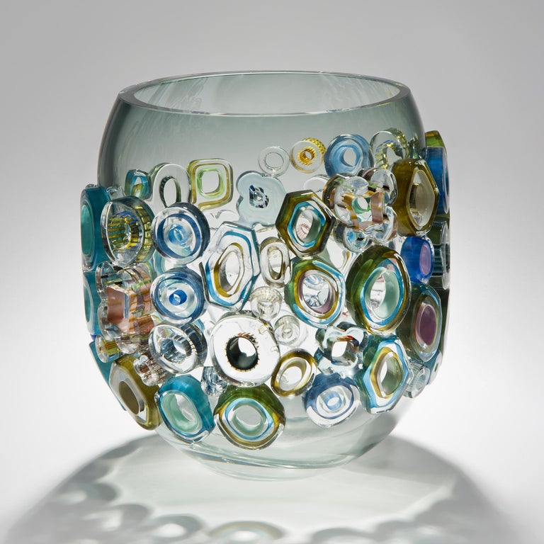 Common ray blue green with green diamonds is a unique hand blown and crafted vase by the German artist, Sabine Lintzen. The initial inner form is free-blown and adorned with various individually shaped murrini, all created in a mix of colored glass