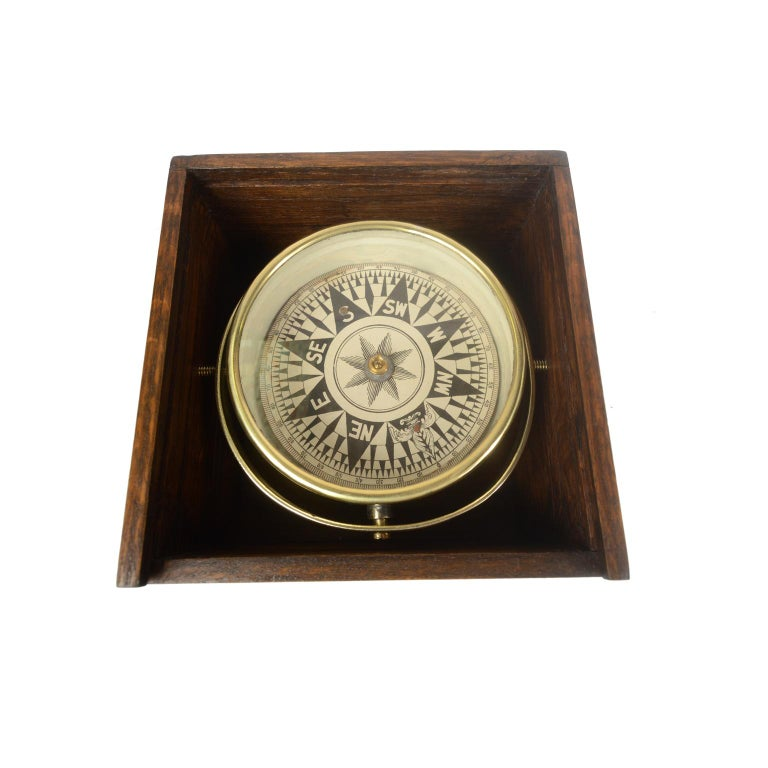 Dry compass in its original wooden box with slot lid. English manufacture from the second half of the 19th century. The compass consists of a brass and glass vessel on the bottom of which a metal stem is fixed on which the eight-wind compass card of