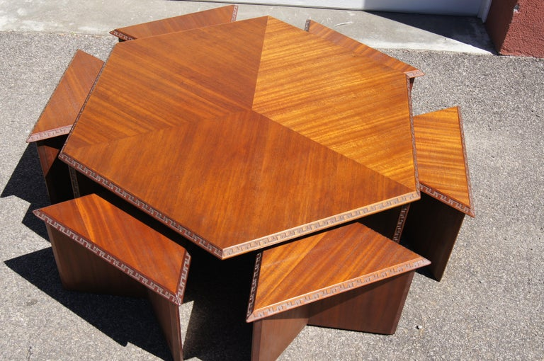 This extraordinary set is part of the Taliesin collection that Frank Lloyd Wright designed for Henredon in 1955. It comprises a mahogany coffee table whose hexagonal top sits on a tripod base and six triangular mahogany stools that slip underneath.