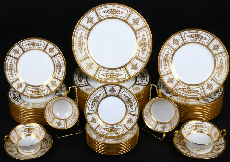 Here is a rare 22-karat gold on ivory ground complete service for 12 from Minton, Stoke-on Trent, England. The set includes dinner, salad, dessert and bread plates, as well as double-handled cream soups with underplates and teacups with saucers. One
