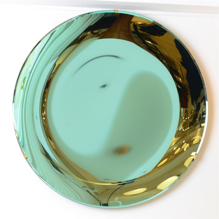 Sculptural green glass concave mirror, with brass wall fixing   Available in pink gold and blue.