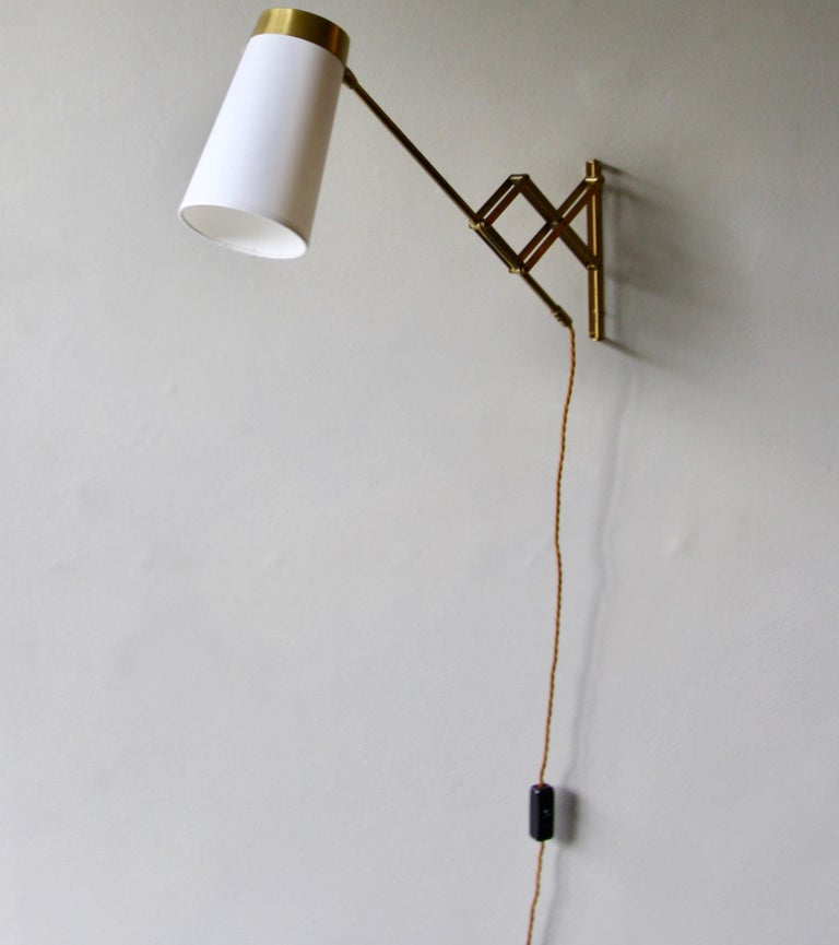 A petite concertina wall light in polished brass, designed and made in Denmark circa 1950.