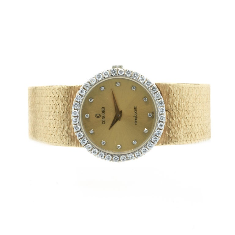 Movement: quartz Function: hours, minutes Case: 24mm 14K yellow gold round case, sapphire crystal, pull/push crown, water resistant, 0.92cttw round brilliant cut diamond bezel Dial: champagne diamond dial Band: Concord 18KY mesh bracelet Serial#:
