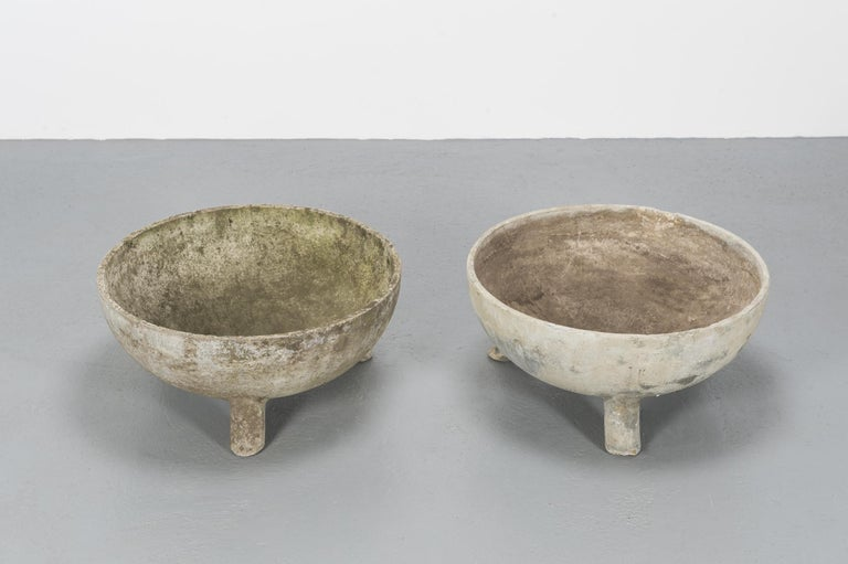 A set of two round large concrete planters in the shape of half bowls, sustained by 3 legs in concrete that lifts them from the ground, protecting the base from deformation and wear. Very good vintage condition.