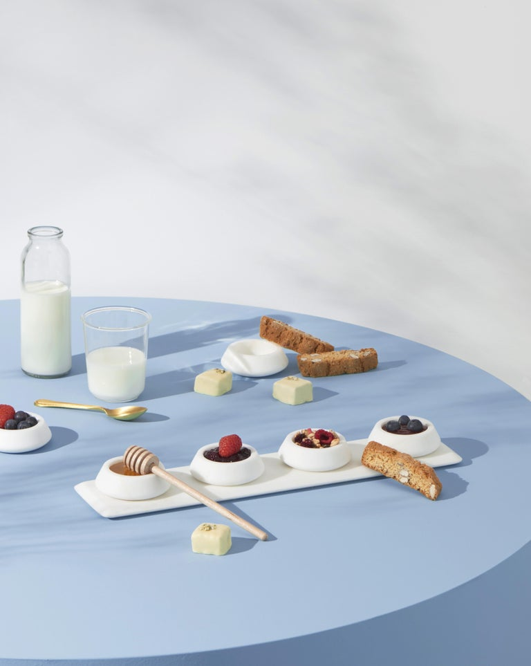 A sculptural shape for a container. Colominas project accomplishes curved marble that lends itself to carrying sauces or oils with designs that are always different. The item includes four white Michelangelo marble bowls. Size: 39.4 x 9 x 1 cm