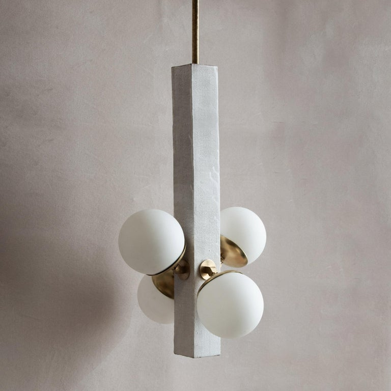 Inspired by midcentury Brutalist architecture and building materials, this playful pendant light balances a strong substantial ceramic base with delicate brass hardware and matte white glass. The substantial ceramic center column is handcrafted from