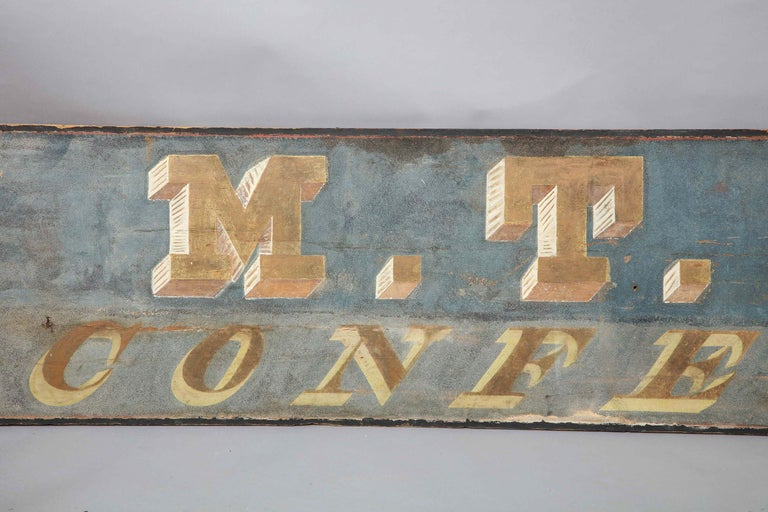Very good mid-19th century painted wooden trade sign from the premises of W.T. Holt, Confectioner, the single plank sign lettered in three dimensional blocked figures piqued in gold and in very graphic type on a powdery blue ground. From a very good